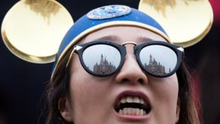 The Enchanted Storybook Castle is reflected in the sunglasses of a girl during the opening ceremony of the Shanghai Disney Resort in Shanghai on June 16, 2016.