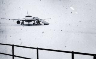 Heavy snow falls on the tarmac of the Glasgow Airport in Glasgow