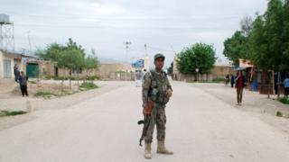 Афганский военный стоит у ворот базы, на которую напали талибы