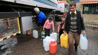 People carry plastic containers with water in Damascus, Syria (16 January 2017)