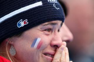 A French coach cries as she watches the medal ceremony of the Alpine Skiing Women's Slalom