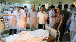 This picture taken on 29 May 2017 shows officials and family members standing next to patients undergoing kidney dialysis in an intensive care unit at hospital in the northern city of Hoa Binh
