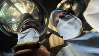 A theatre nurse and a surgeon holding a scalpel perform an operation