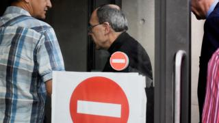 Cardinal Barbarin arrives at a police station in Lyon early on 8 June