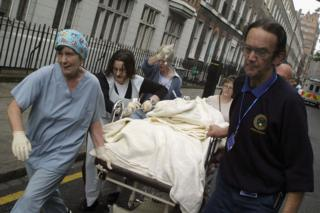 Emergency workers take a body on a stretcher from Russell Square tube station