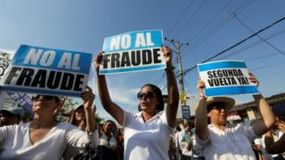 """People hold signs reading """"No to fraud"""" and """"(Election) Run-off now"""" as they protest near the electoral council in Guayaquil, Ecuador February 20, 2017."""
