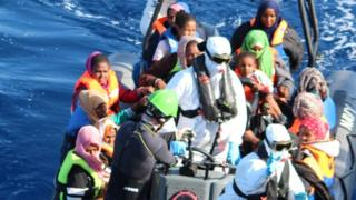 Crew members of the LÉ Róisín on a small boat with rescued migrants