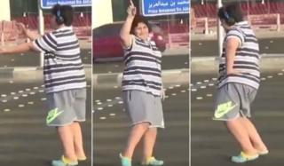 Three collaged screengrabs show a teen wearing a striped shirt and sport shorts at various stages of doing the popular Macarena dance in a Saudi street