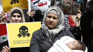 A woman with a baby in a crowd of protesters