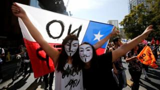 Demonstrators wear Guy Fawkes masks during a march against the national pension system, in Santiago, Chile