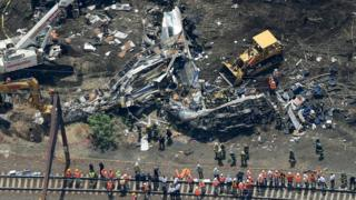 Investigators and first responders work near the wreckage of Amtrak Northeast Regional Train 188, from Washington to New York, that derailed yesterday May 13, 2015 in north Philadelphia