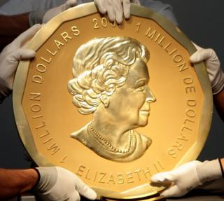 "Picture taken in Vienna, Austria on June 25, 2010 shows experts of an Austrian art forwarding company holding one of the world""s largest gold coins, a 2007 Canadian $ 1,000,000 ""Big Maple Leaf"". An identical coin was stolen from Berlin""s Bode Museum on March 27, 2017."