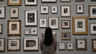 A member of staff poses in front of photographs belonging to Elton John during a press preview for The Radical Eye: Modernist Photography from The Sir Elton John Collection at Tate Modern