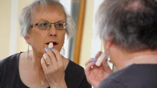 Penny applies lipstick