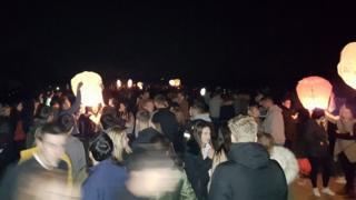 People releasing lanterns