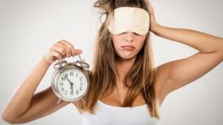 ผู้หญิงถือนาฬิกาปลุกตอนเพิ่งตื่น