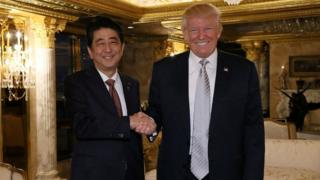 Shinzo Abe shakes hands with Donald Trump