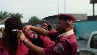 महिला कर्मचारियों के बाल काटते अधिकारी