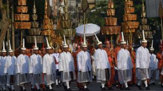 Men in ceremonial uniforms walk in a procession transporting the royal urn containing the remains of Thailand's most senior Buddhist monk, the late Supreme Patriarch Somdet Phra Nyanasamvara, in Bangkok
