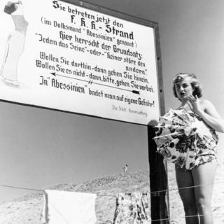 Mujer en una playa nudista en Alemania al lado de un cartel del movimiento FKK.