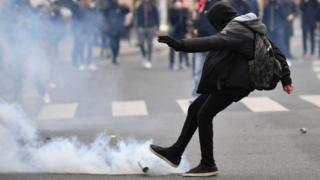 A protester kicks a tear gas canister during the demonstration in Paris (23 February 2017)