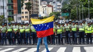 "A member of the Venezuela""s opposition gestures showing a national flag in front of National policemen during a demonstration in Caracas on July 27, 2016."