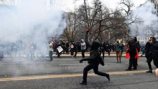 A protester lobs a brick at police during protests in Washington during the inauguration of Donald Trump