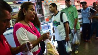 People buy bread in a bakery in Caracas, on September 14, 2016.