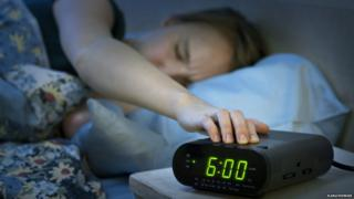 Женщина, отключающая будильник
