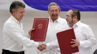 El presidente de Cuba, Raúl Castro, observa a su homólogo de Colombia, Juan Manuel Santos (izq.) darse la mano con el líder de las FARC Rodrigo Londoño, alias Timochenko, tras firmar un acuerdo de cese el fuego en La Habana, Cuba.