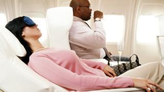 Пассажирка спит, откинувшись в кресле