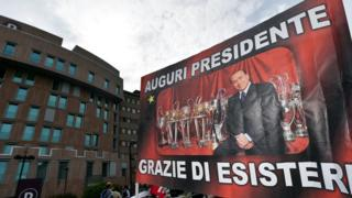 """""""All the best, president - thanks for being there"""", a banner reads outside the hospital in Milan where Mr Berlusconi underwent the operation"""