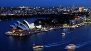 A night view of the Sydney Opera House and the city beyond