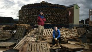 Douglas (L) and Darren McDowell (R) pose with their creation as work continues on the Sandy Row bonfire on July 10, 2017 in Belfast, Northern Ireland.