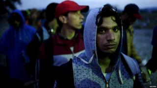 Migrants wait to enter a transit camp after entering the country by crossing the border with Greece