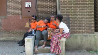 Erricka Bridgeford, con polo naranja a la derecha, se sienta con su amiga Ellen Gee, de blanco, y sus hijos, afuera de un inmueble abandonado.
