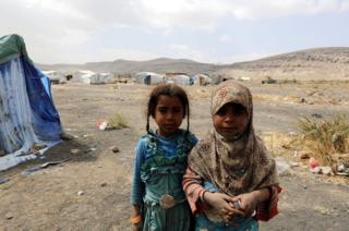 Two sisters in the camp stare into the camera