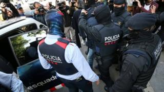 Spanish police put one of the nine detained suspects in a police car in Barcelona. Photo: 25 April 2017