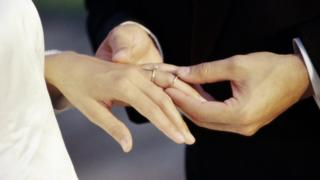 A groom putting a ring on the bride's finger