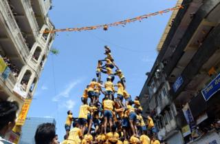 Indian Hindu devotees attempt to form a human pyramid in a bid to reach and break a dahi-handi (curd-pot) suspended in the air during celebrations for the Janmashtami festival, which marks the birth of Hindu God Lord Krishna in Mumbai on September 6, 2015.
