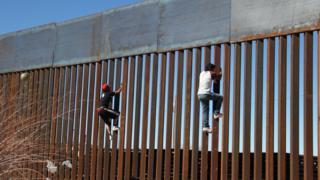 Boys climb border fence at Ciudad Juarez
