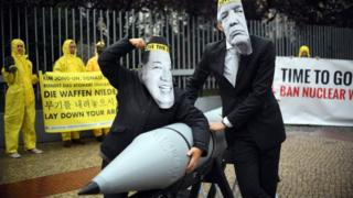 Activists dressed as Donald Trump and Kim Jong Un, tussle over a nuclear bomb in ican protest