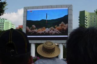 Decenas de ciudadanos ven el lanzamiento de lo que Corea del Norte llamó un misil balístico intercontinental este 4 de julio en una pantalla colocada en la estación central de tren de Pyongyang.