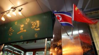 The national flags of North Korea and China are hung in front of a North Korean restaurant October 9, 2006 at the border city of Dandong, Liaoning Province of China.