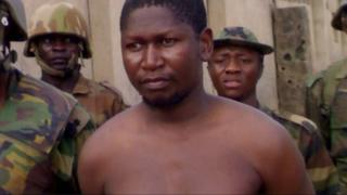 Mohammed Yusuf, bare-chested and with a bandage on his arm, surrounded by soldiers
