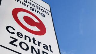 A picture of congestion charge sign close up, with a clear sky in the background.