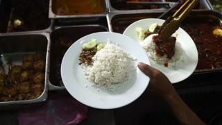 In this picture taken 25 March 2015 a Malaysian stall assistant serves Nasi Lemak dish on a plate at the 'Nasi Lemak Tanglin' stall in Kuala Lumpur