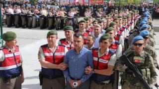 Айыпталуучулардын катарынан тизип алып сот залына алып келе жаткан учурда президент Реджеп Тайип Эрдогандын жактоочулары чогулуп турушту.