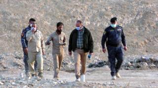 نیروهای عراقی و کارشناسان پزشکی قانونی در محل گور جمعی