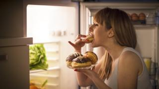 Woman eating donuts from the fridge